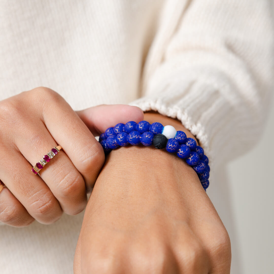 Girl wearing a silicone beaded bracelet with Aquarius symbol pattern on wrist.