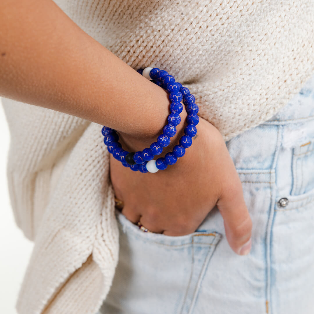 Girl wearing a silicone beaded bracelet with Aries symbol pattern on wrist.