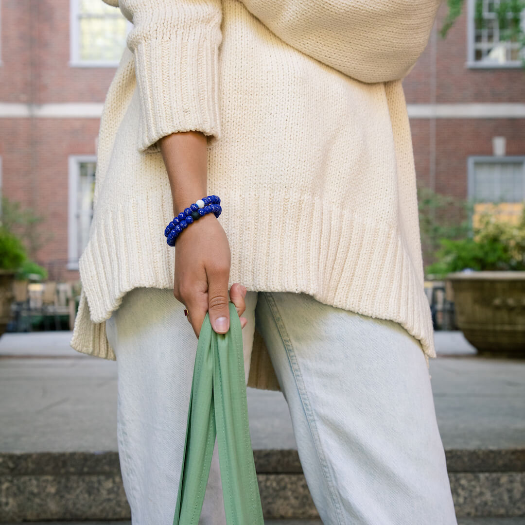 Girl holding a bag wearing  a silicone beaded bracelet with Aries symbol pattern on wrist.