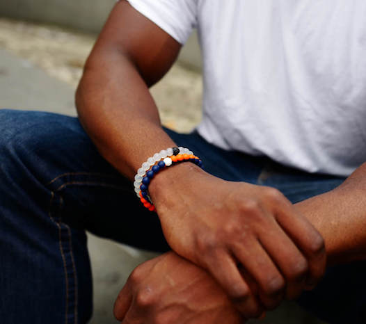 Man holding his wrist while wearing an orange and blue silicone beaded bracelet.