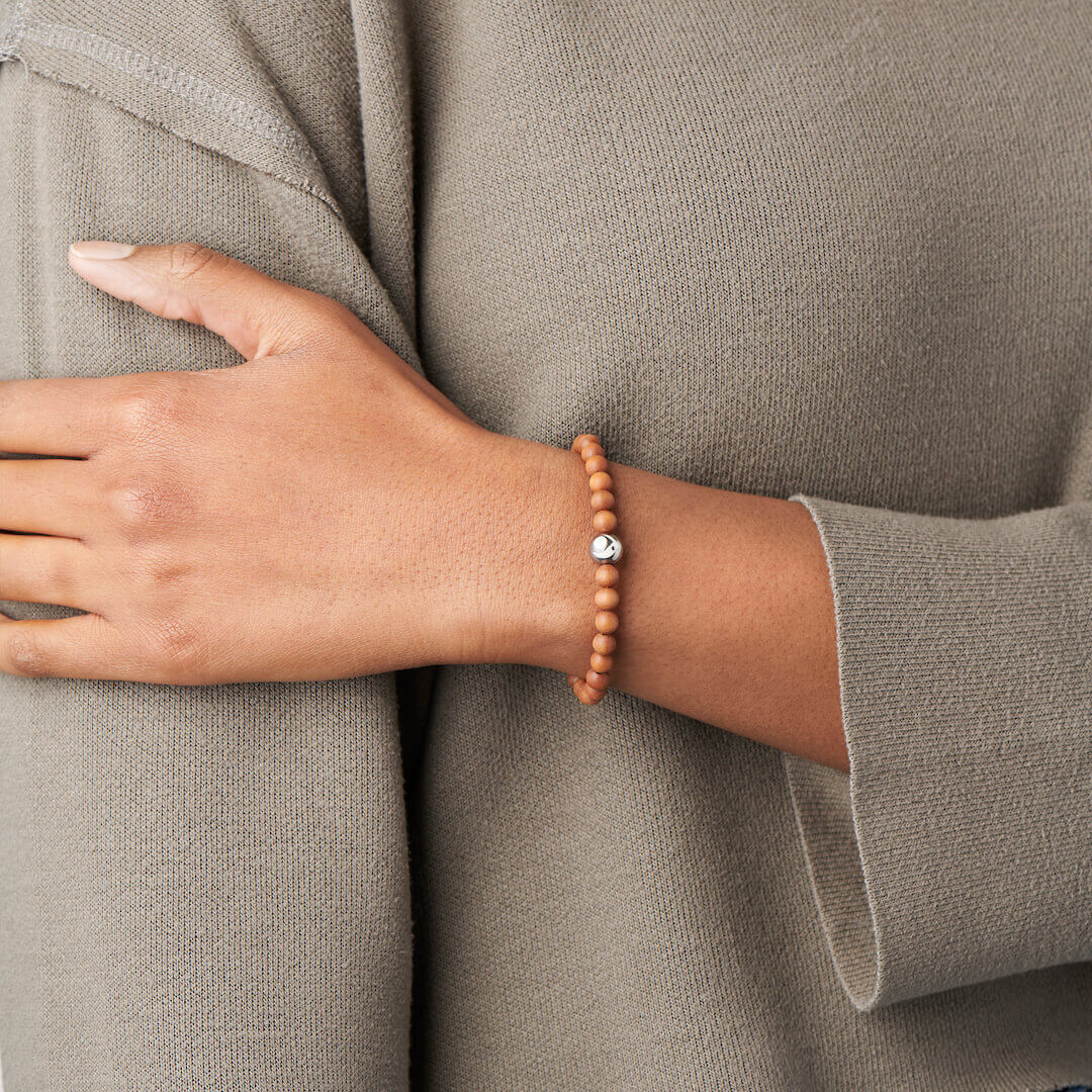 Person wearing a wood bead bracelet with lokai symbol on either side.