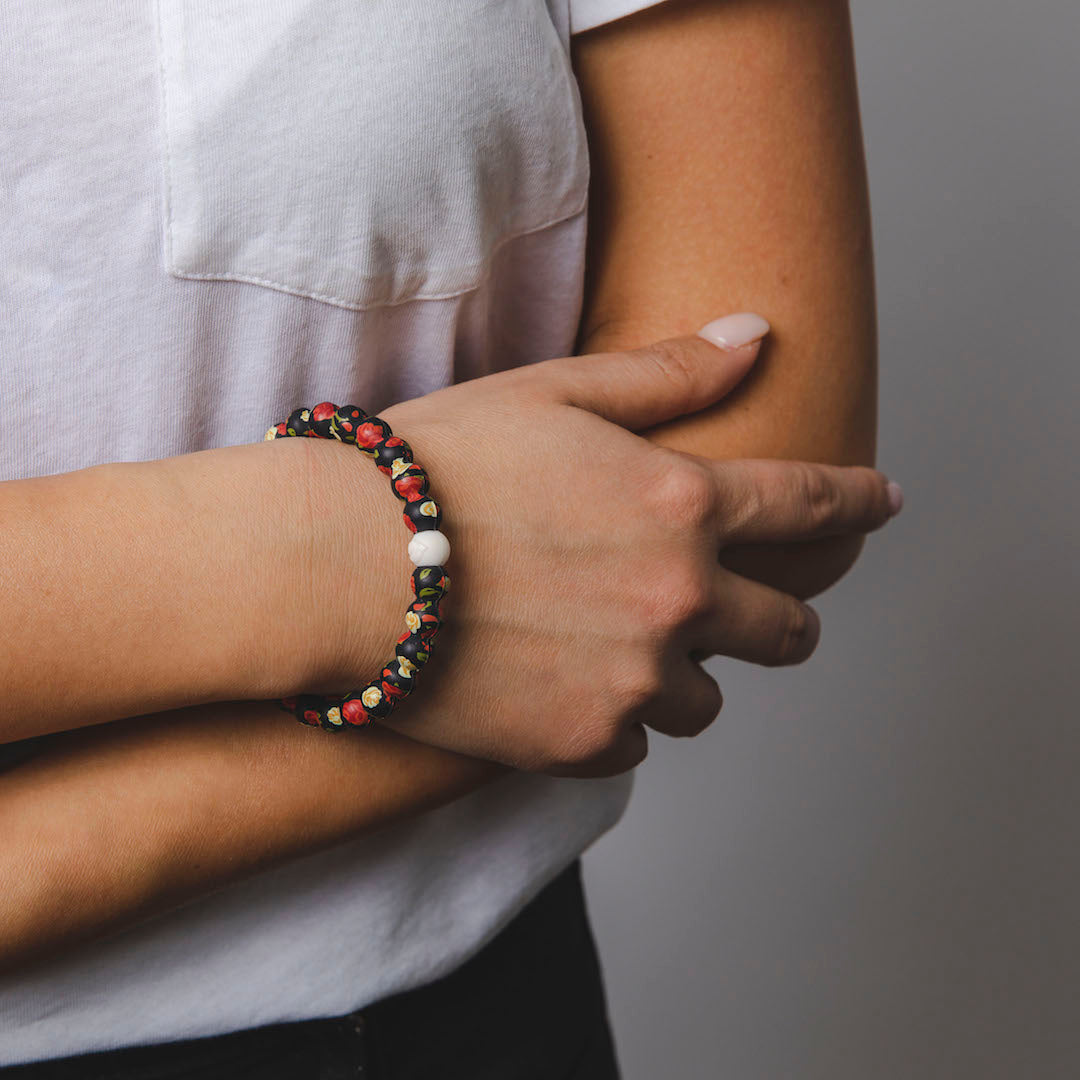 Woman wearing silicone beaded bracelet with rose pattern on wrist