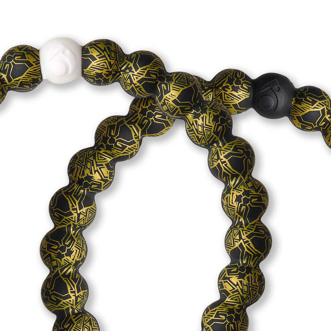Close up of silicone beaded bracelet with black and gold Black Panther pattern.