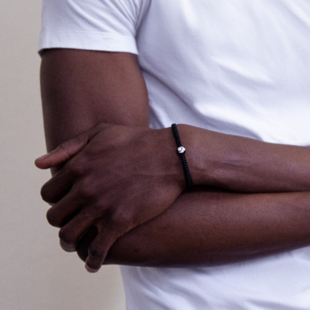 Male wearing black woven bracelet on wrist with arms crossed.
