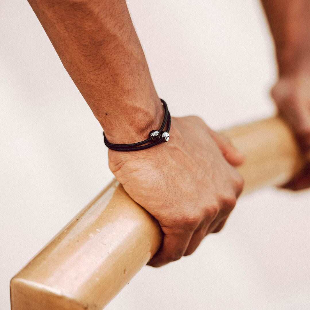 Close up of male wearing black cord bracelet on wrist while resting his hands on a wooden bar.