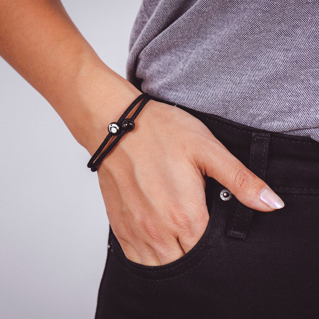 Close up of woman wearing black cord bracelet with two gunmetal metal beads on wrist with her hand in her pocket.