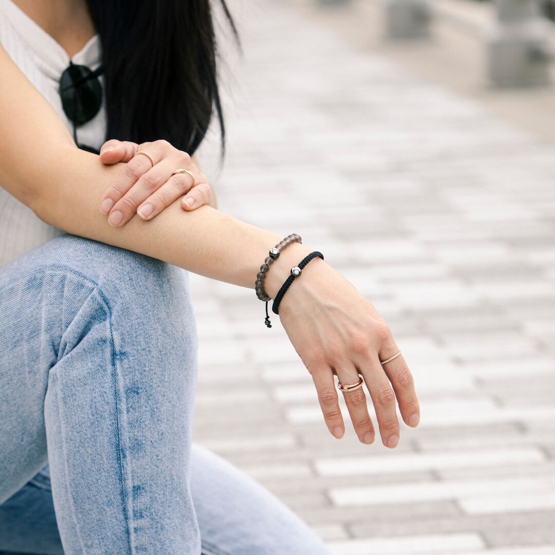 Woman wearing transparent smoke glass bead bracelet on wrist while kneeling down and resting her arm on her leg.