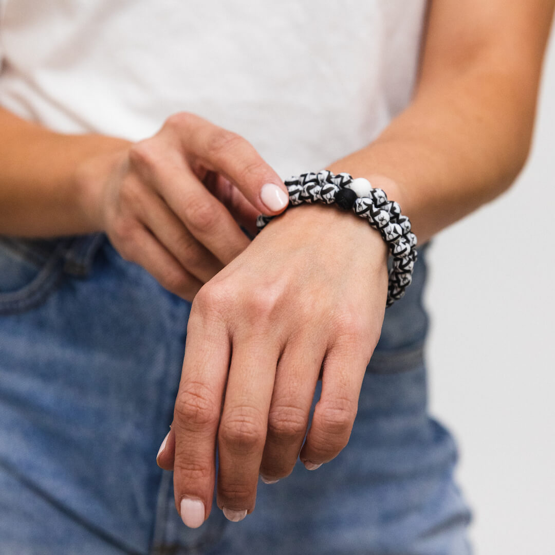 Woman wearing a silicone beaded bracelet with black widow spider pattern on wrist.