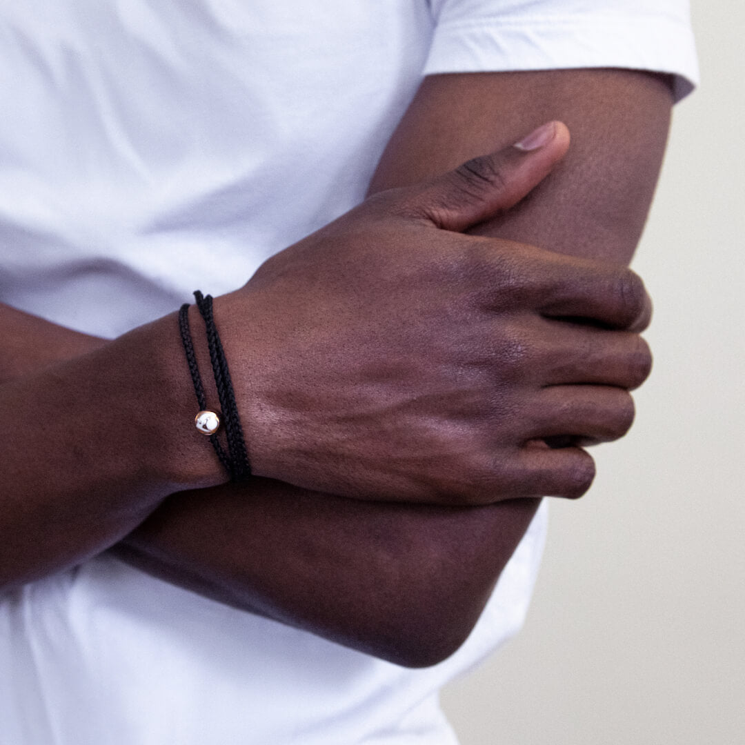 Male wearing black triple wrap woven bracelet on wrist with his arms crossed.