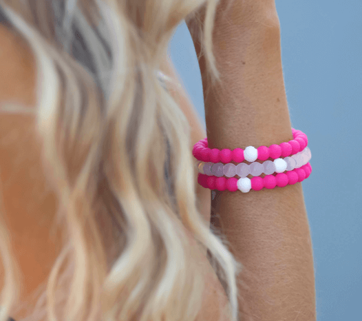 Close up of stack of hot pink and clear silicone beaded bracelets on female wrist.
