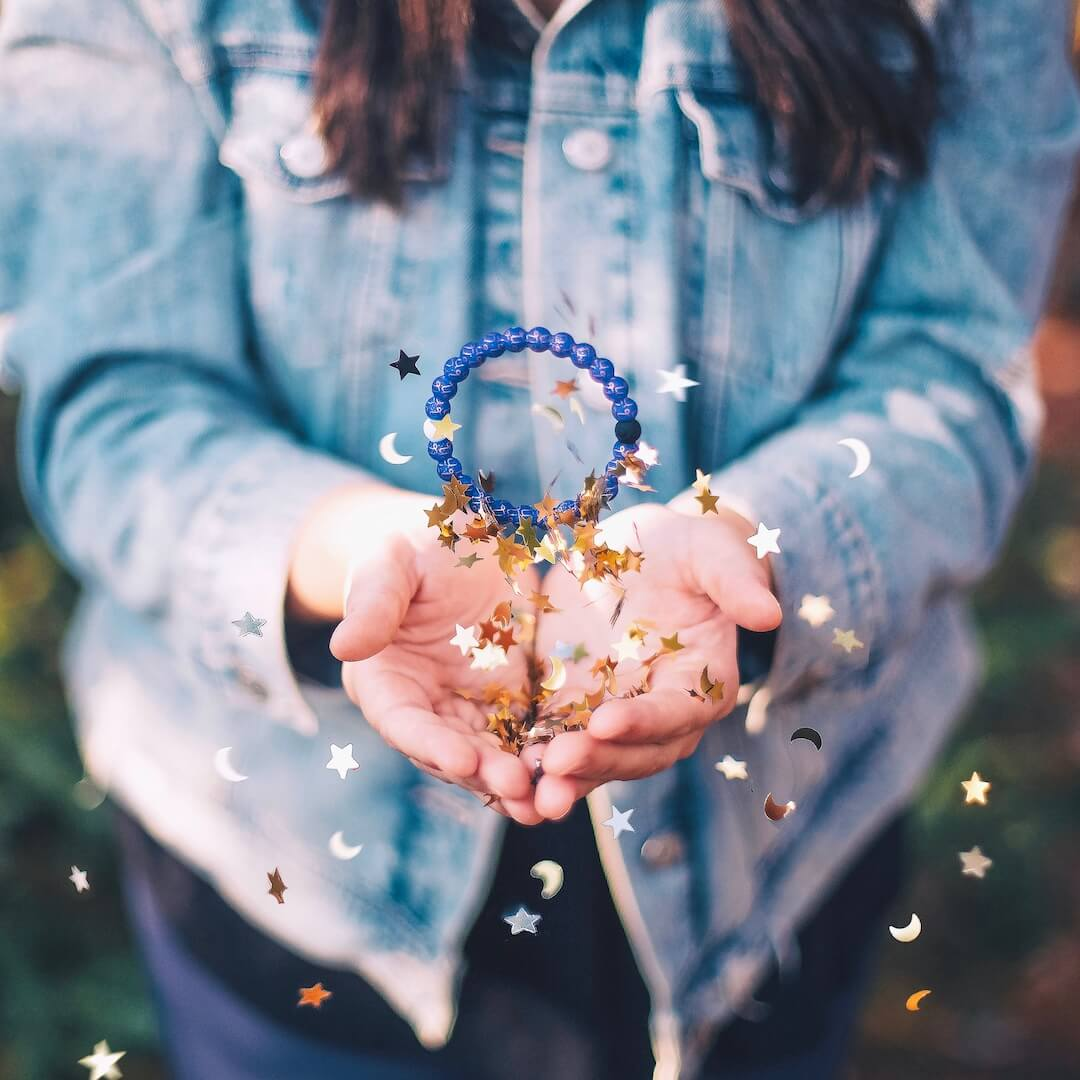 Girl throwing a silicone beaded bracelet with Capricorn symbol pattern in the air with moon and stars confetti.