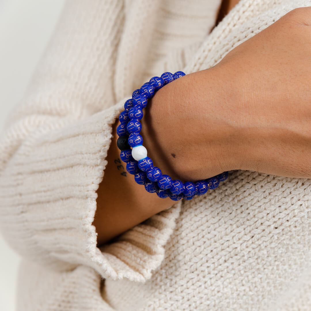 Girl wearing a silicone beaded bracelet with Capricorn symbol pattern on wrist.