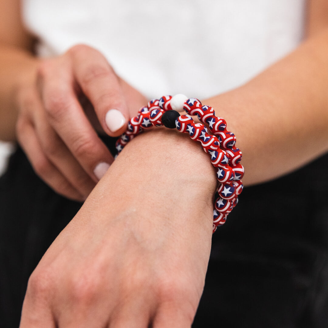 Woman wearing two silicone beaded bracelet with Captain America's shield pattern on wrist.