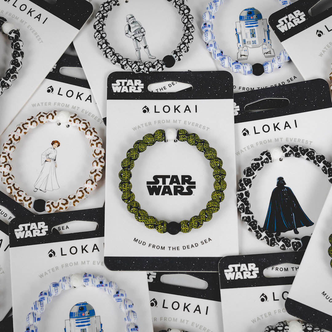 Pile of silicone beaded bracelets on carded back with various Star Wars patterns.