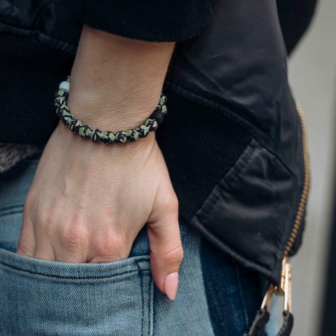 Woman with hand in back pocket wearing silicone beaded bracelet on wrist with The Child pattern.