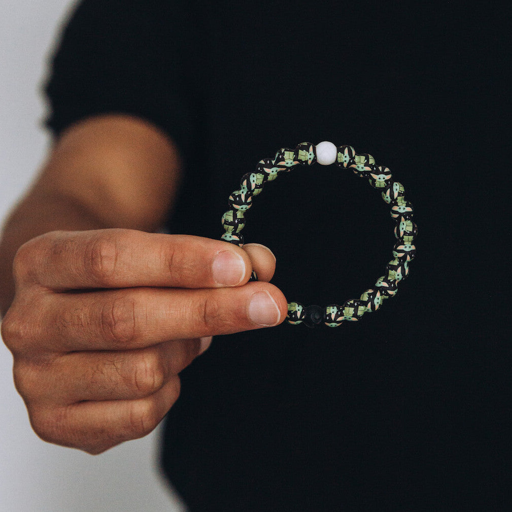 Close up of man holding silicone beaded bracelet with The Child pattern.