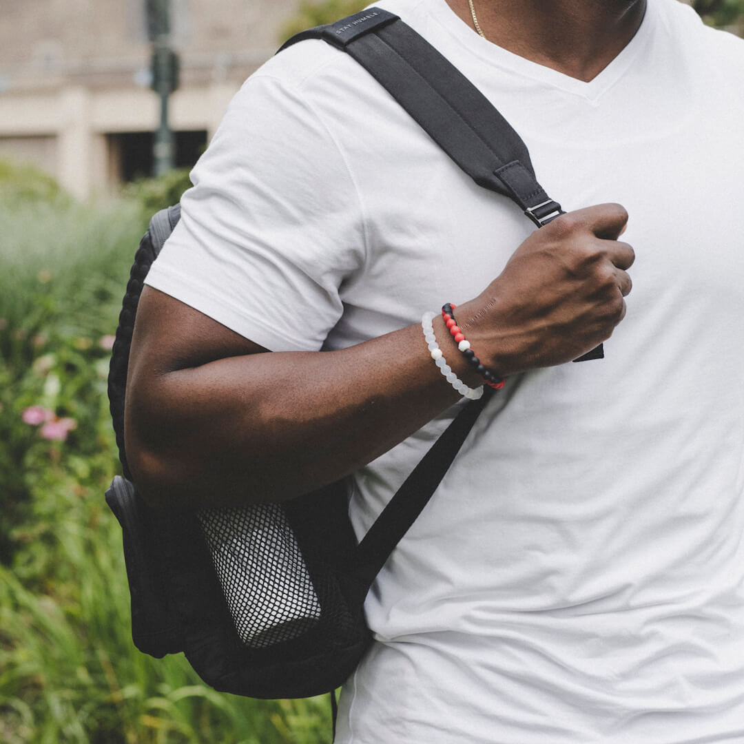 Man holding backpack wearing a red and black silicone beaded bracelet.