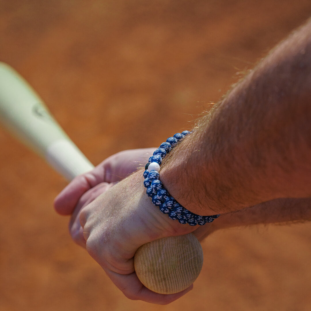 Man holding a baseball bat wearing a silicone beaded bracelet with New York Yankees Logo pattern.