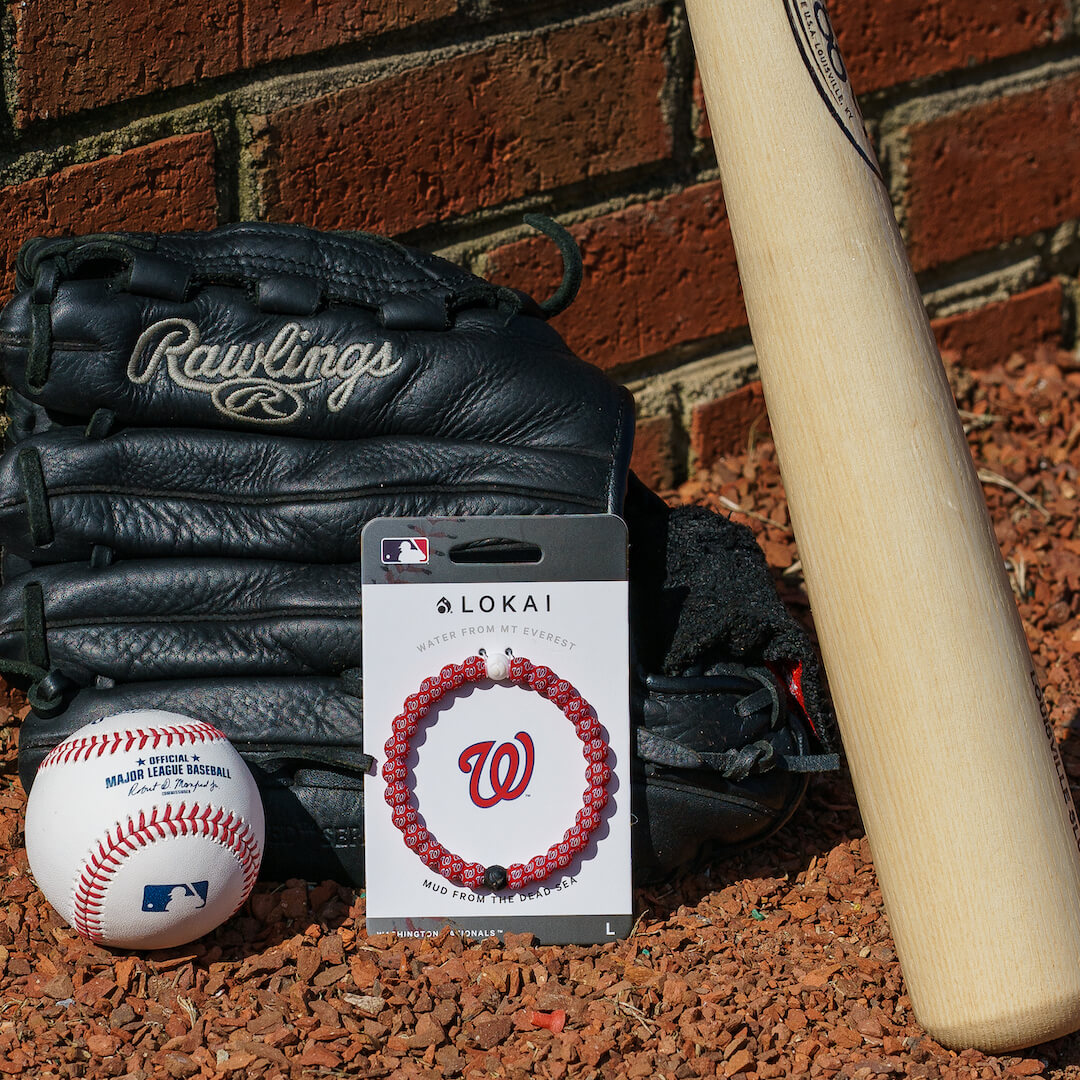 A baseball, mitten, and bat with a silicone beaded bracelet with Washington Nationals logo pattern.