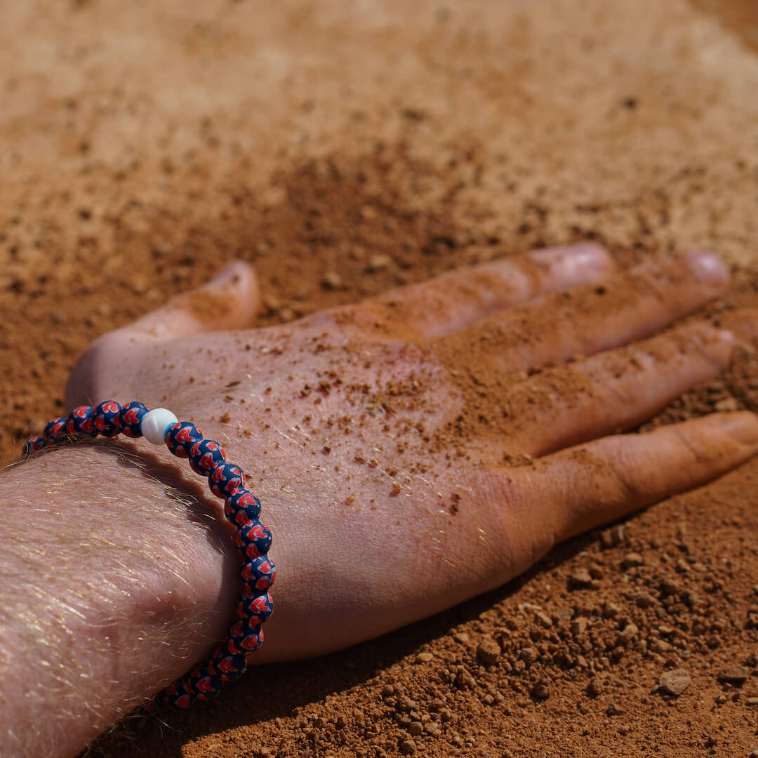 A man with his hand in dirt wearing a silicone beaded bracelet with a Boston Red Sox logo.
