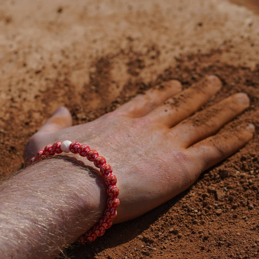 Man with hand in dirt wearing a silicone beaded bracelet with Philadelphia Phillies logo pattern.
