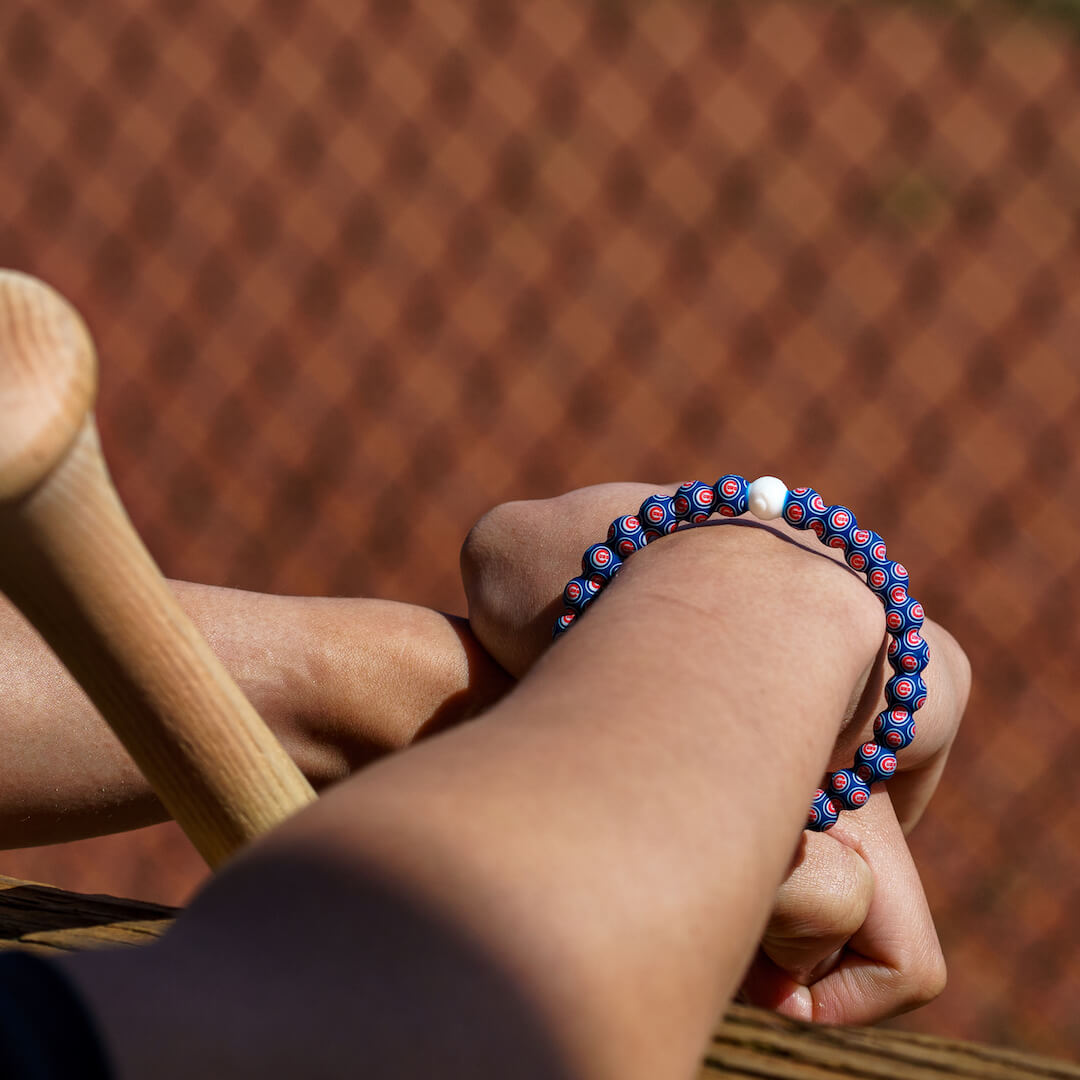 Person with baseball bat wearing a silicone beaded bracelet with Chicago Cubs logo pattern.