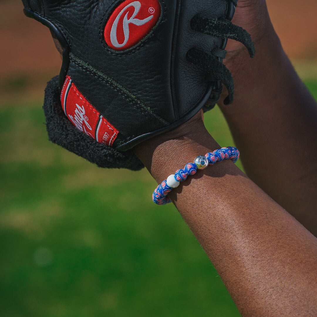 Man wearing a baseball mitten wearing a silicone beaded bracelet with Chicago Cubs logo pattern.