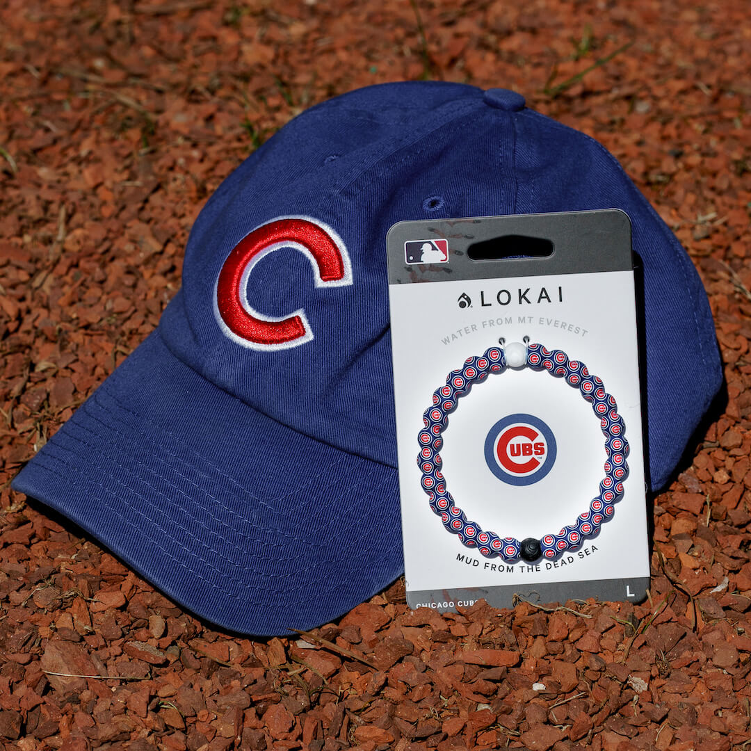 Baseball hat next to a silicone beaded bracelet with Chicago Cubs logo pattern.