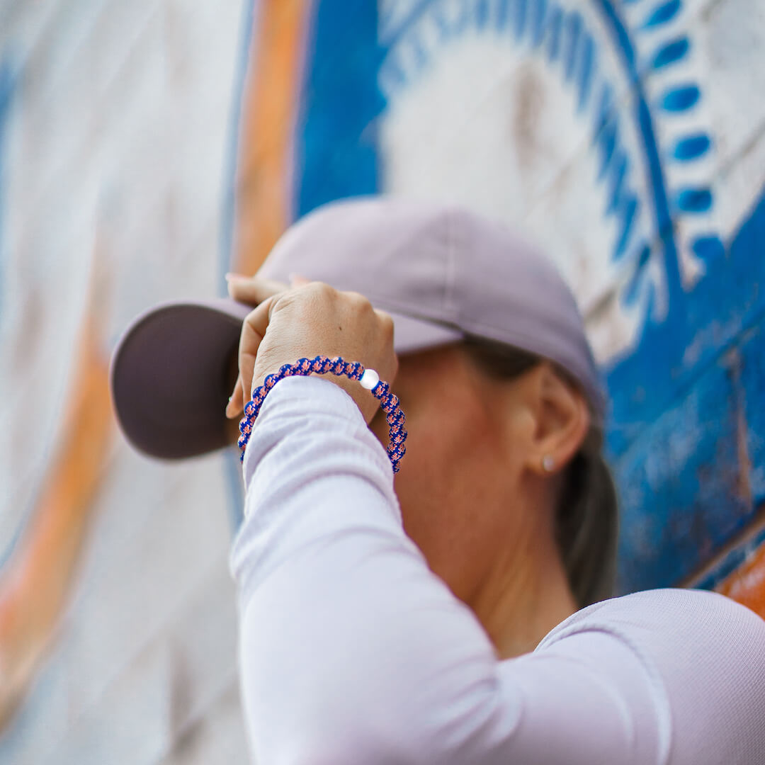 Woman holding a hat wearing silicone beaded bracelet with New York Mets logo pattern.