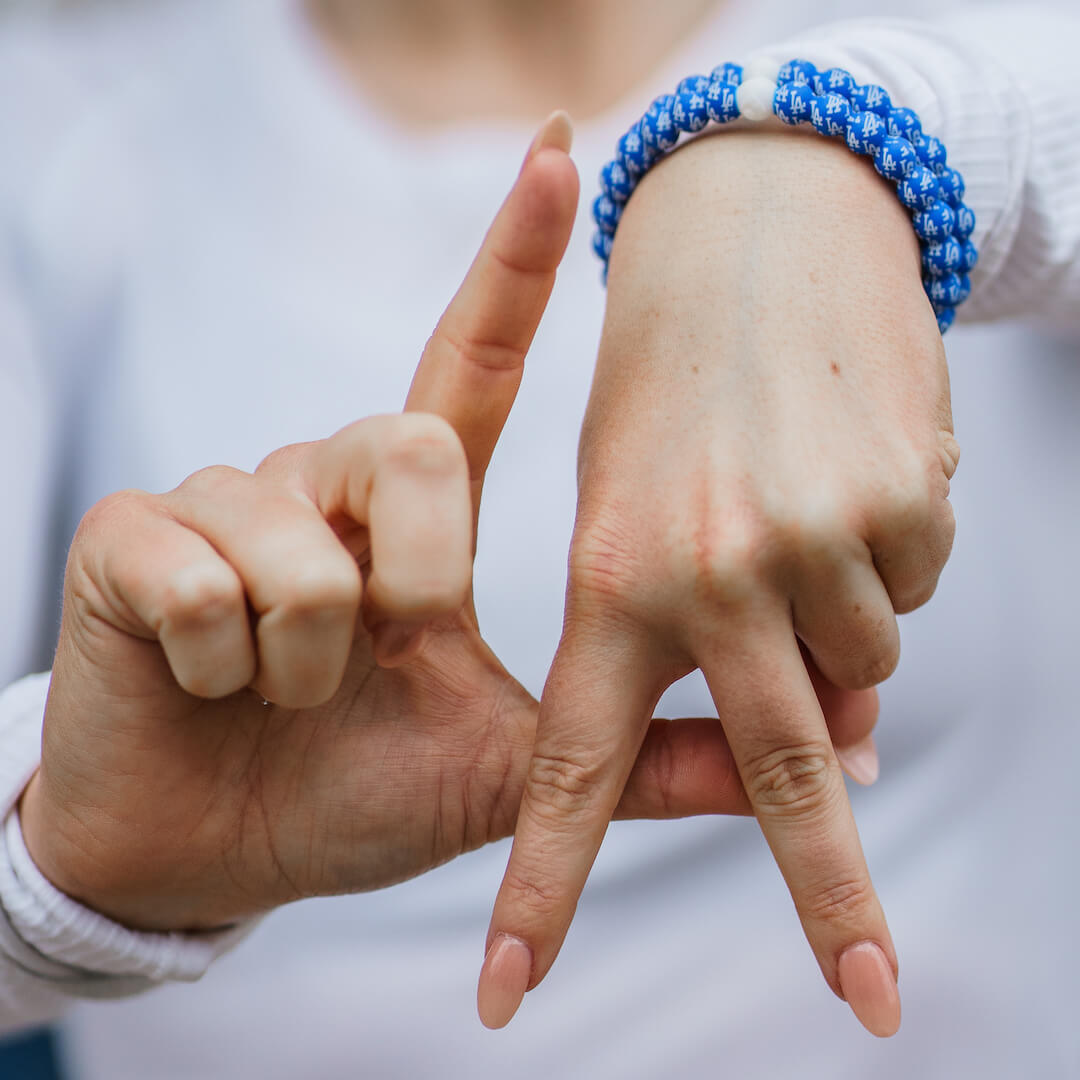 Woman gesturing the LA Dodgers symbol wearing a silicone beaded bracelet with LA Dodgers logo pattern.