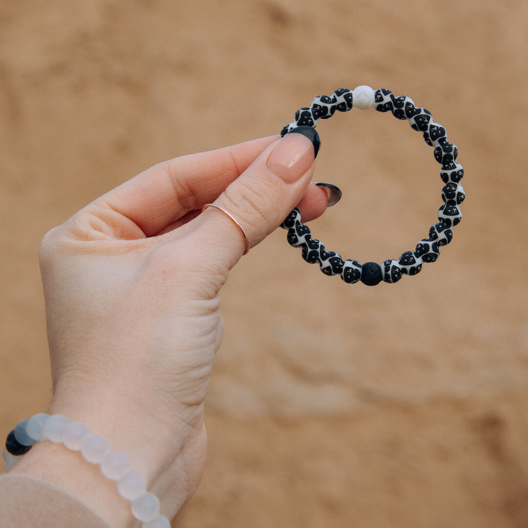 Close up of hand holding silicone beaded bracelet with Darth Vader pattern.