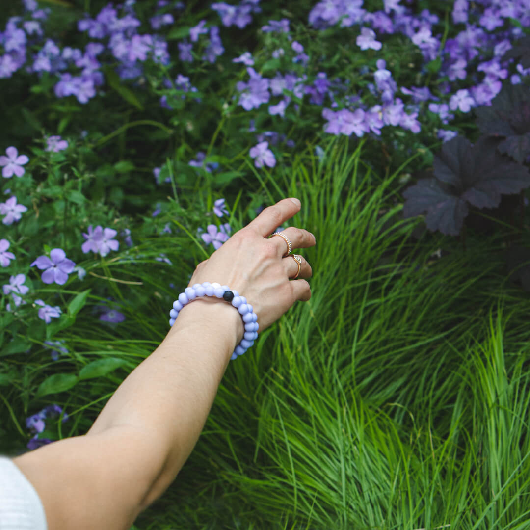 Female reaching towards purple flowers wearing a light purple silicone beaded bracelet on her wrist.