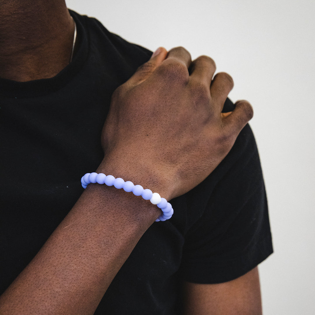 Male wearing light purple silicone beaded bracelet on wrist with hand on shoulder.