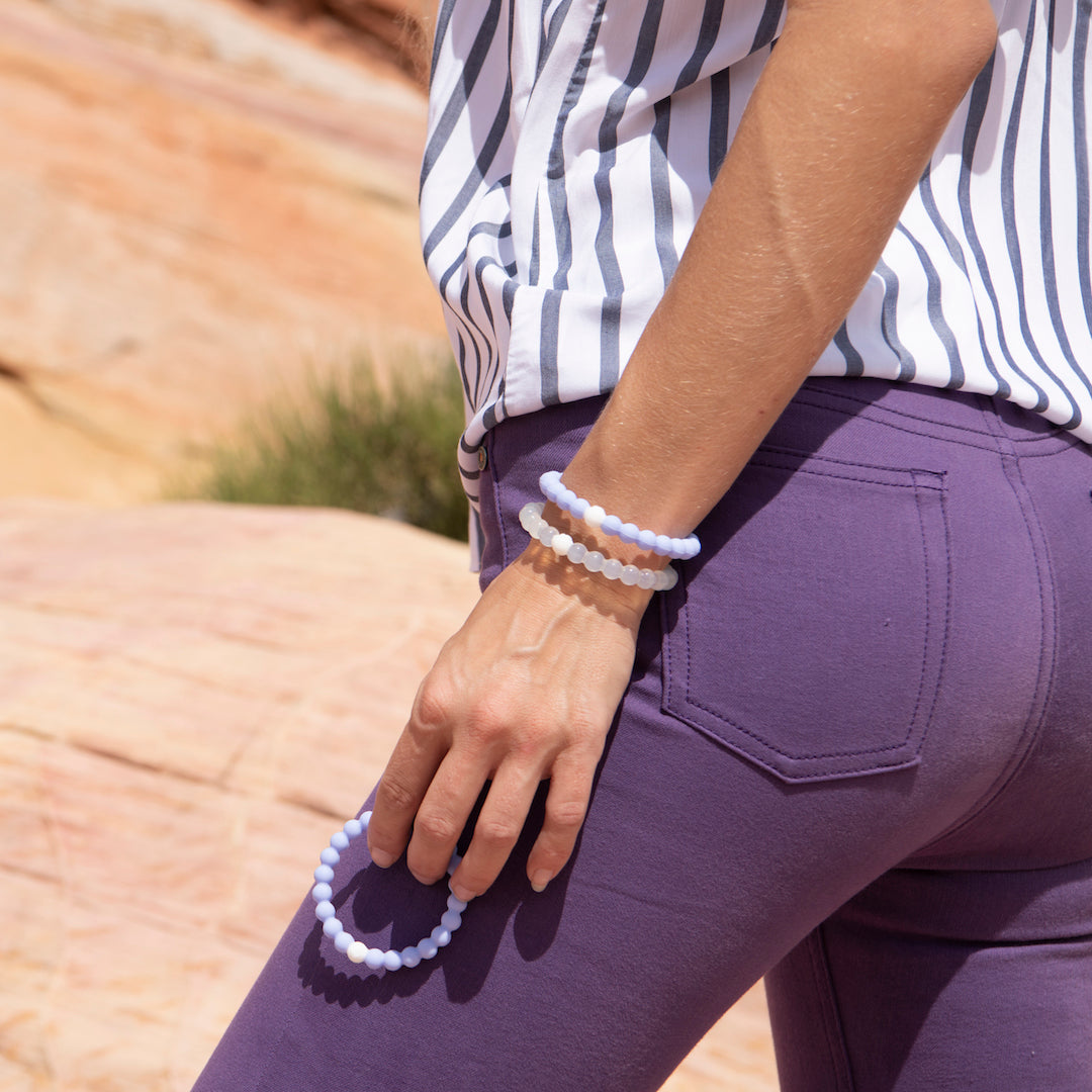 Female wearing purple pants and holding light purple silicone beaded bracelet by her leg.