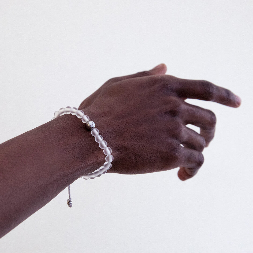 Male wearing clear glass bead bracelet on wrist while holding hand out.