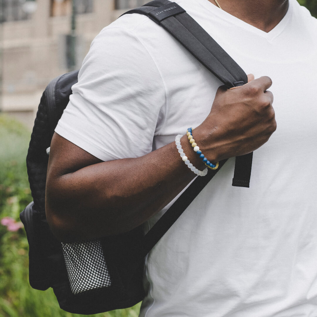Man holding backpack wearing beige and blue silicone beaded bracelet.