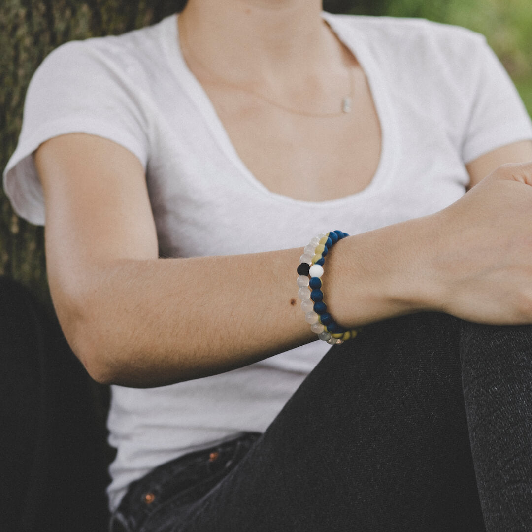 Woman with arms on legs wearing beige and blue silicone beaded bracelet
