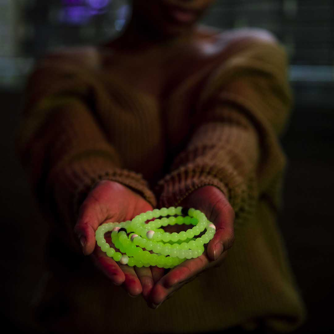 Female in tan sweater holding a pile of glow in the dark silicone beaded bracelets.