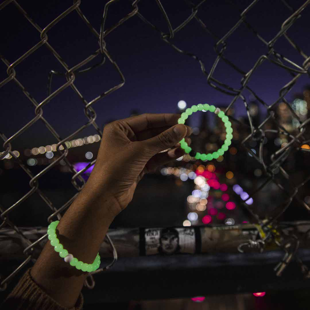 Woman holding a glow in the dark silicone beaded bracelet in front of a chain link fence.