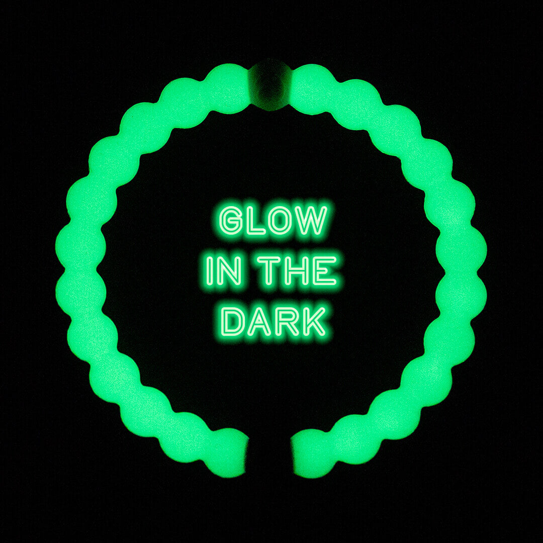Glow in the dark silicone beaded bracelet on a black background with the words