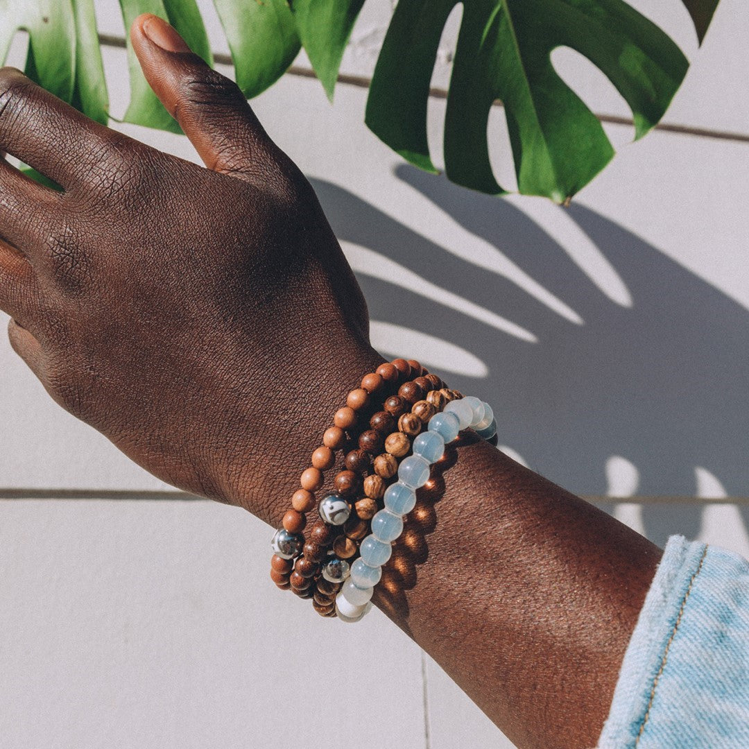 Person wearing golden sandalwood beaded bracelet with lokai symbol on either side.