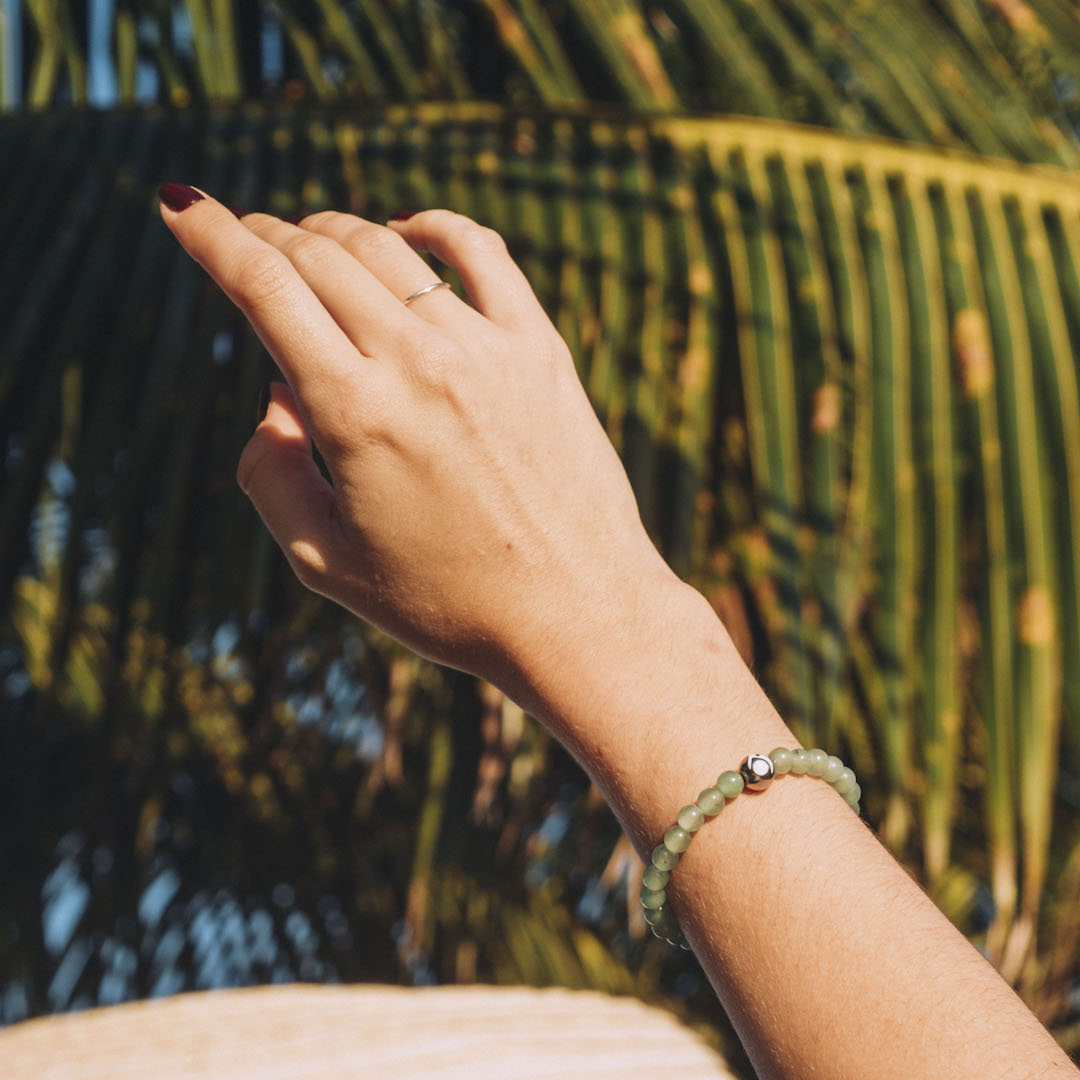 Female wearing green stone bracelet on wrist with palm tree in background.