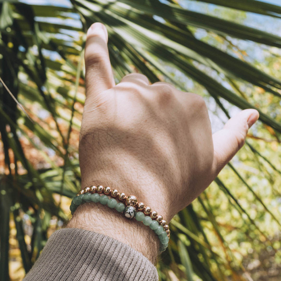 Close up of rose gold metal bead bracelet with palm tree in the background.