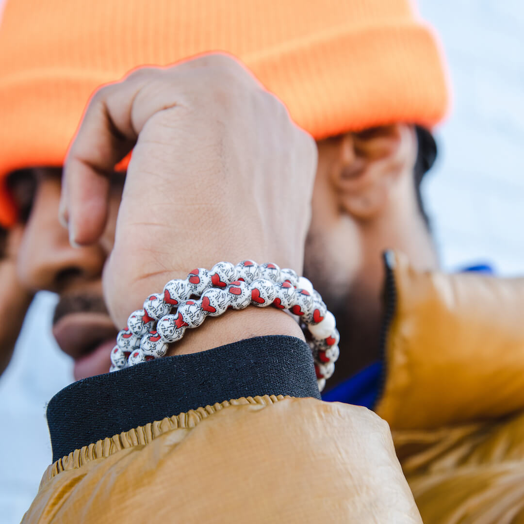 Man wearing a silicone beaded bracelet with Keith Haring Heart pattern on wrist.