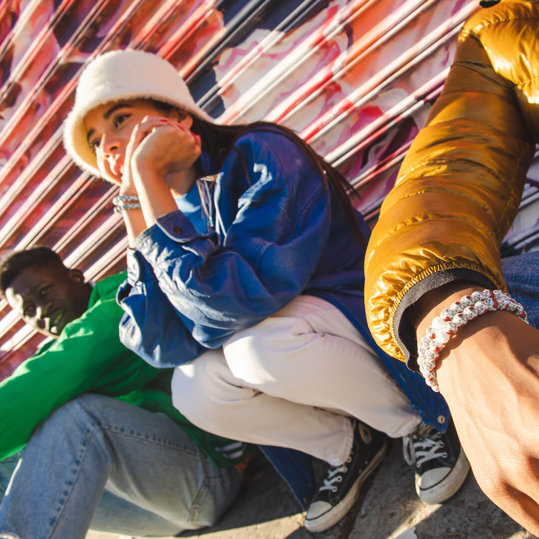 Group of people sitting on the sidewalk all wearing silicone beaded bracelets with Keith Haring Heart patterns on wrist.