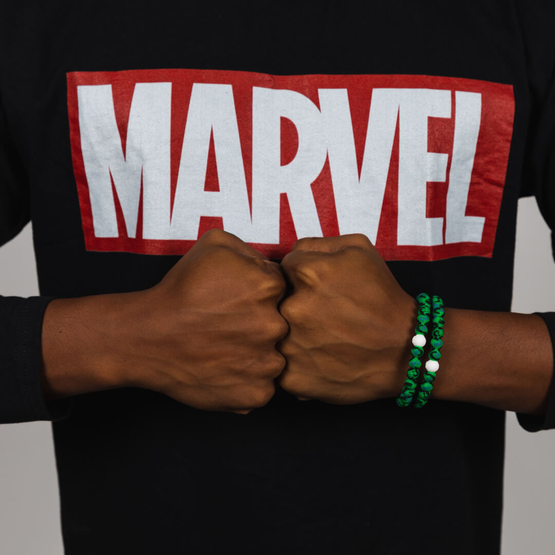 Man wearing two silicone beaded bracelets with Hulk fist pattern on wrist.