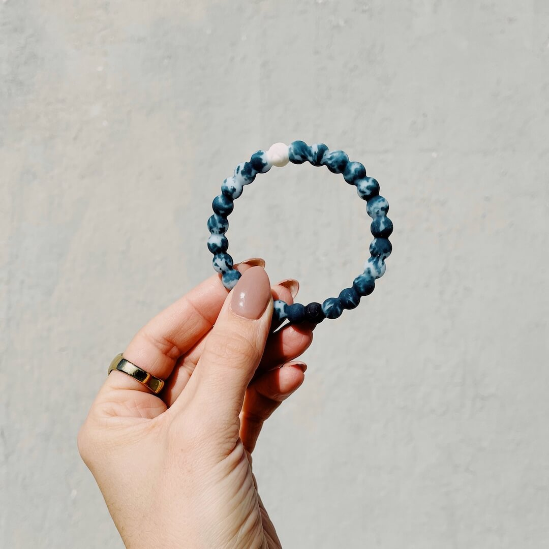 Woman holding a turquoise and light blue tie-dye silicone beaded bracelet.