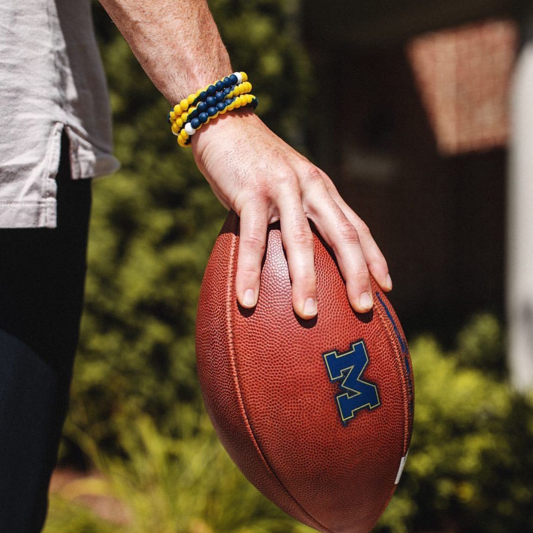 Man holding a football wearing a yellow and dark blue silicone beaded bracelet.
