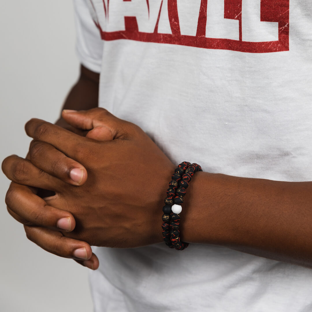 Man wearing a silicone beaded bracelet with Iron Man pattern on wrist.