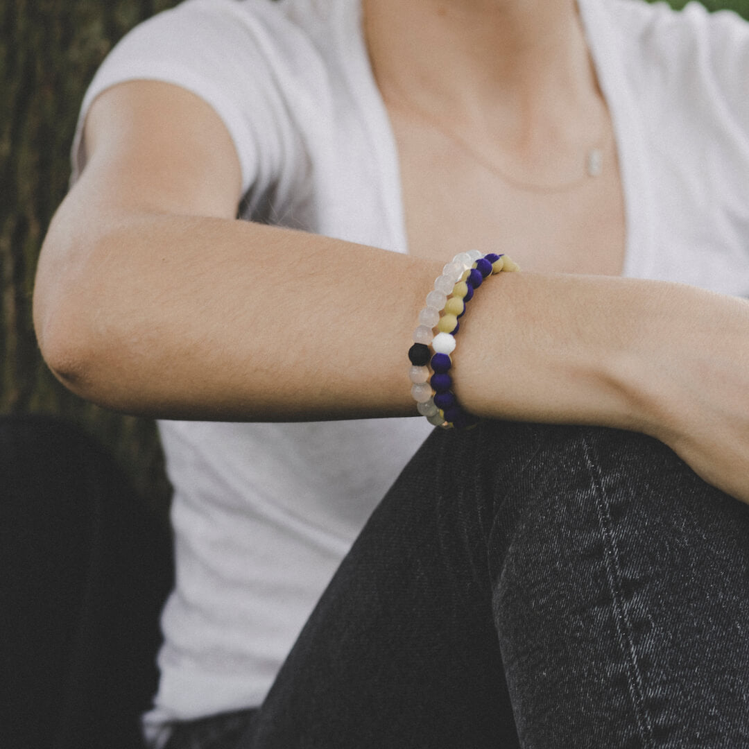 Close-up of a woman wearing a purple and gold silicone beaded bracelet.